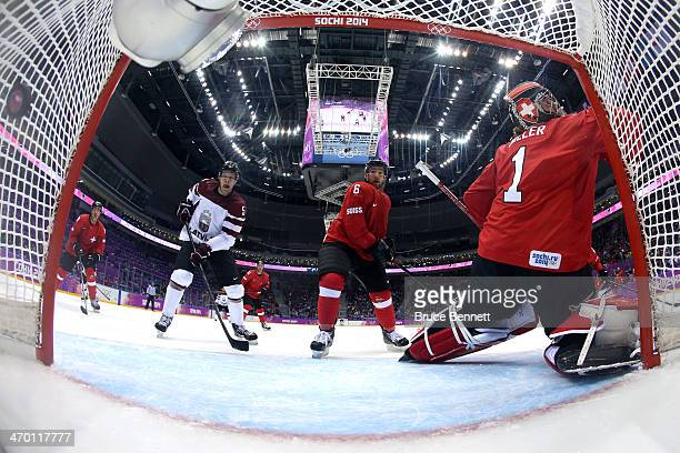Jonas Hiller of Switzerland gives up a goal in the first period to Lauris Darzins of Latvia during the Men's Ice Hockey Qualification Playoff game on...