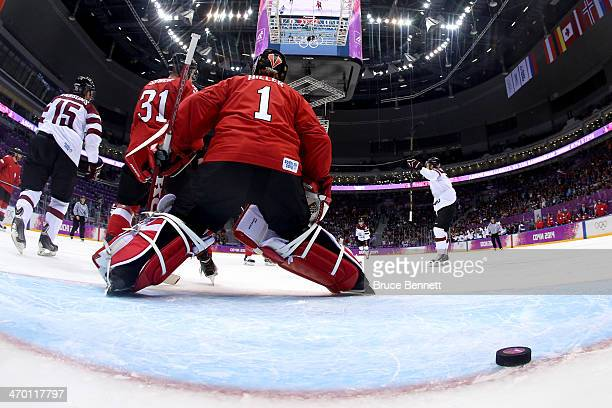 Jonas Hiller of Switzerland gives up a goal in the first period to Oskars Bartulis of Latvia during the Men's Ice Hockey Qualification Playoff game...