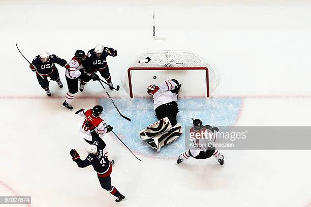 Jonas Hiller of Switzerland knocks the puck into his own goal after time had expired in the second period during the ice hockey men's quarter final...