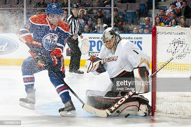 Jonas Hiller of the Anaheim Ducks makes a save against Taylor Hall of the Edmonton Oilers at Rexall Place on January 13, 2012 in Edmonton, Alberta,...