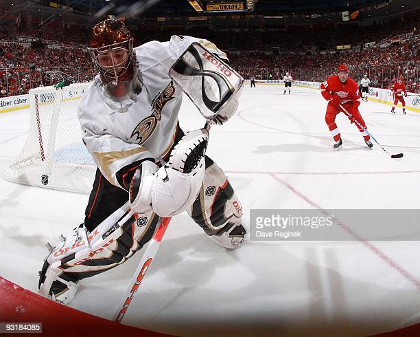 Jonas Hiller of the Anaheim Ducks stops the puck behind the net as Drew Miller of the Detroit Red Wings closes in during a NHL game at Joe Louis...