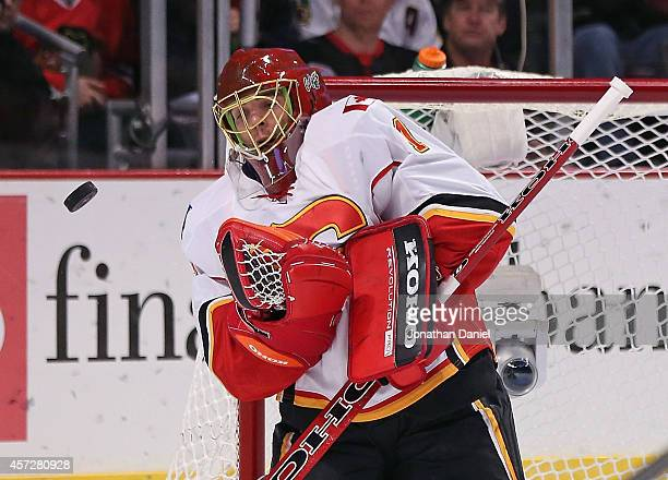 Jonas Hiller of the Calgary Flames makes a save against the Chicago Blackhawks at the United Center on October 15, 2014 in Chicago, Illinois. The...