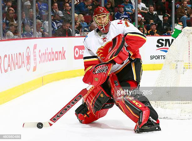Jonas Hiller of the Calgary Flames plays the puck during their NHL game against the Vancouver Canucks at Rogers Arena December 20 2014 in Vancouver...