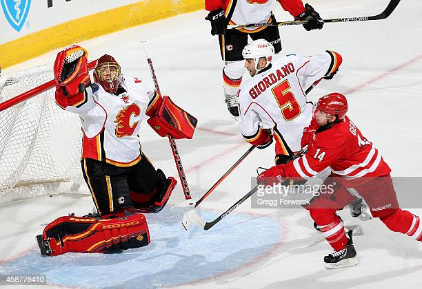 Jonas Hiller of the Calgary Flames reaches up to block a shot from Nathan Gerbe of the Carolina Hurricanes during their NHL game at PNC Arena on...
