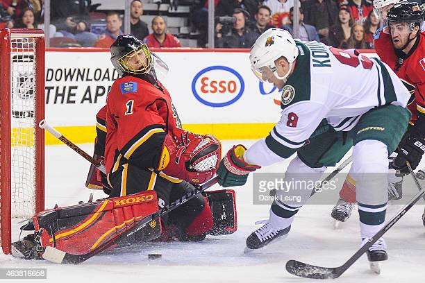 Jonas Hiller of the Calgary Flames stops the shot of Mikko Koivu of the Minnesota Wild during an NHL game at Scotiabank Saddledome on February 18...