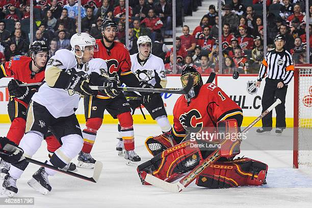 Jonas Hiller of the Calgary Flames stops the shot of Sidney Crosby of the Pittsburgh Penguins during an NHL game at Scotiabank Saddledome on February...