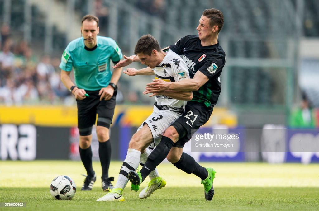 Jonas Hofmann of Borussia Moenchengladbach and Dominik Kohr of FC Augsburg battle for the ball during the Bundesliga Match between Borussia Moenchengladbach and FC Augsburg at Borussia-Park on May 06, 2017 in Moenchengladbach, Germany.