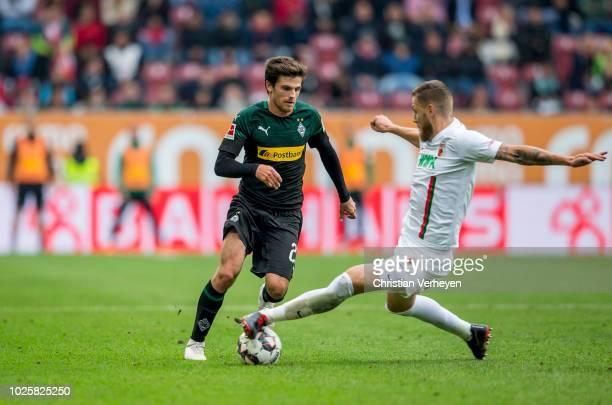 Jonas Hofmann of Borussia Moenchengladbach and Jeffrey Gouweleeuw of FC Augsburg battle for the ball during the Bundesliga match between FC Augsburg...