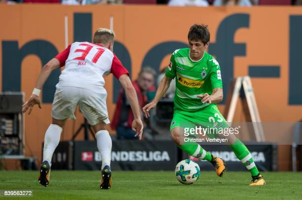Jonas Hofmann of Borussia Moenchengladbach is chased by Philipp Max of FC Augsburg during a Bundesliga match between FC Augsburg and Borussia...