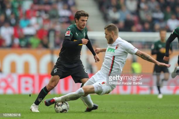 Jonas Hofmann of Moenchengladbach challenges Jeffrey Gouweleeuw of Augsburg during the Bundesliga match between FC Augsburg and Borussia...