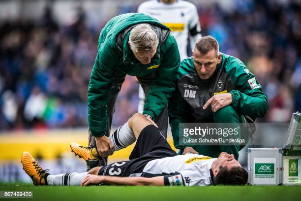 Jonas Hofmann of Moenchengladbach gets medical attention from doctor Stefan Hertl and Dirk Mueller during the Bundesliga match between TSG 1899...