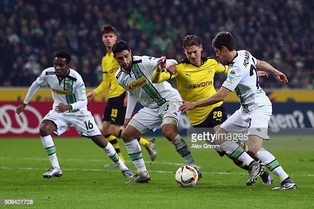 Jonas Hofmann of Moenchengladbach is challenged by Lukas Piszczek of Dortmund during the Bundesliga match between Borussia Moenchengladbach and...