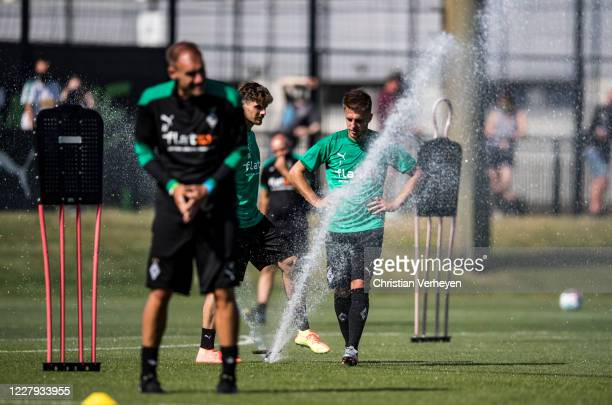 Jonas Hofmann, Patrick Herrmann and Assistant Coach Alexander Zickler cool down during a training session of Borussia Moenchengladbach at...