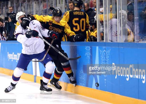 Jonas Holos of Norway and David Wolf of Germany compete for the puck during the Men's Ice Hockey Preliminary Round Group B game on day nine of the...