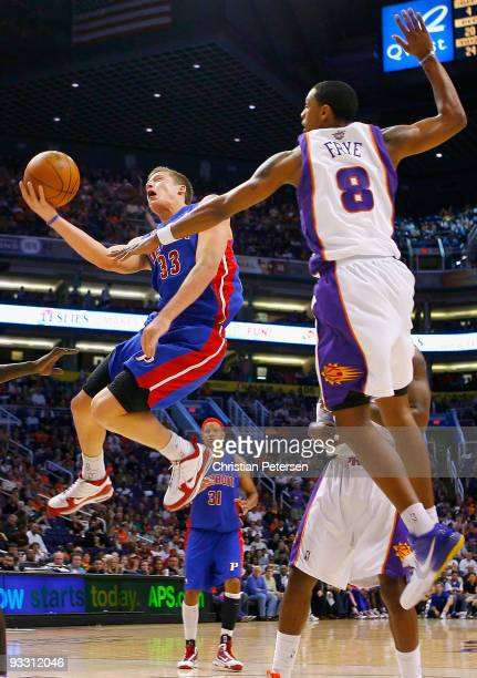 Jonas Jerebko of the Detroit Pistons lays up a shot past Channing Frye of the Phoenix Suns during the NBA game at US Airways Center on November 22...