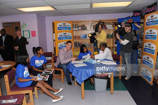 Jonas Jerebko of the Detroit Pistons lends his moral support as a student prepares for her vaccination as part of the Detroit Pistons NBA Vaccines...