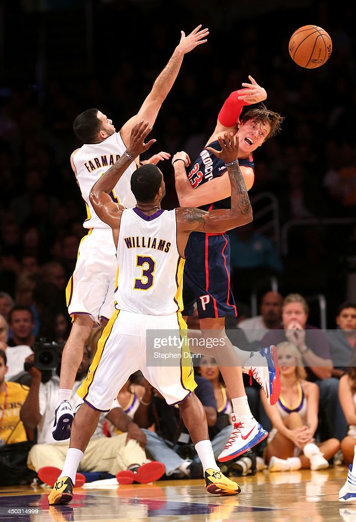 Jonas Jerebko #33 of the Detroit Pistons passes off the ball away from Jordan Farmar #1 and Shawne Williams #3 of the Los Angeles Lakers at Staples Center on November 17, 2013 in Los Angeles, California.