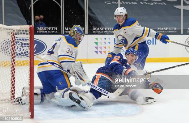 Jonas Johansson and Jack Eichel of the Buffalo Sabres defend against Casey Cizikas of the New York Islanders at the Nassau Coliseum on March 04, 2021...