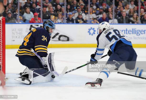 Jonas Johansson of the Buffalo Sabres makes a save on Jansen Harkins of the Winnipeg Jets during the first period at KeyBank Center on February 23...