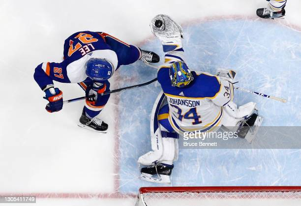 Jonas Johansson of the Buffalo Sabres makes the save on Anders Lee of the New York Islanders at the Nassau Coliseum on March 04, 2021 in Uniondale,...