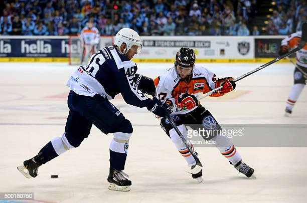 Jonas Liwing of Hamburg Freezers battles for the puck with Sbastian Furchner of Grizzly Wolfsburg during the DEL game between Hamburg Freezers and...