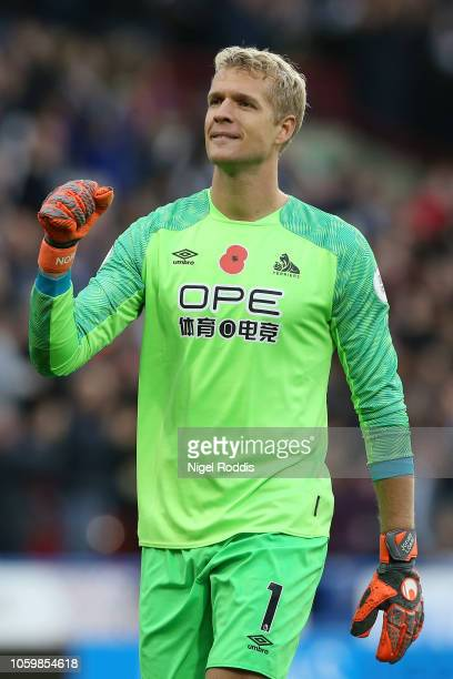 Jonas Lossl of Huddersfield Town celebrates after teammate Alex Pritchard scores their team's first goal during the Premier League match between...