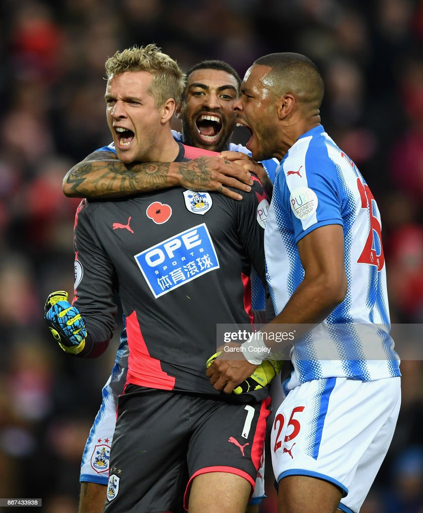 Jonas Lossl of Huddersfield Town celebrates saving a penalty with Danny Williams of Huddersfield Town and Mathias Jorgensen of Huddersfield Town during the Premier League match between Liverpool and Huddersfield Town at Anfield on October 28, 2017 in Liverpool, England.