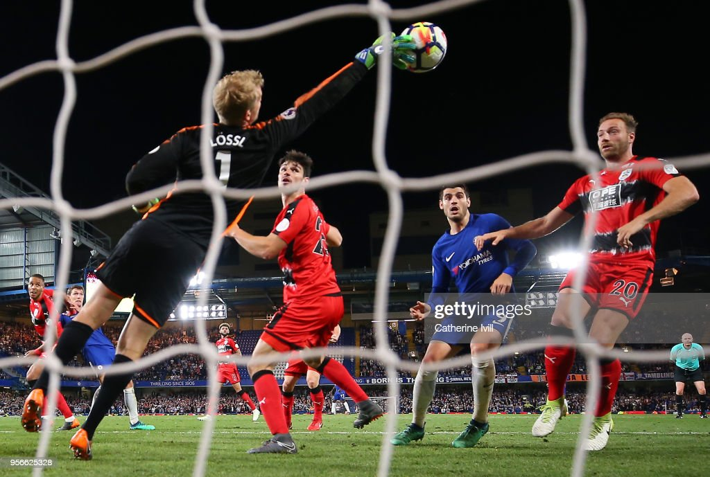 Jonas Lossl of Huddersfield Town makes a save as Alvaro Morata of Chelsea and Laurent Depoitre of Huddersfield Town looks on during the Premier League match between Chelsea and Huddersfield Town at Stamford Bridge on May 9, 2018 in London, England.