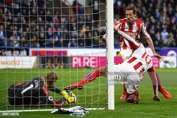 Jonas Lossl of Huddersfield Town saves the ball on the line from an over head kick by Maxim ChoupoMoting of Stoke City during the Premier League...