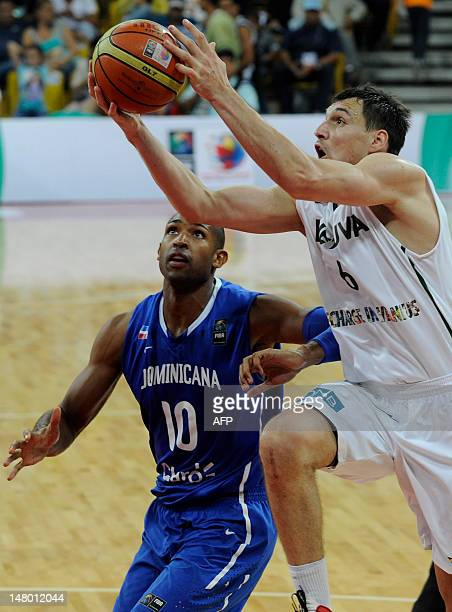 Jonas Maciulis of Lithuania tries to score a basket against Al Harford of Dominican Republic during their PreOlympic basketball game in Caracas on...