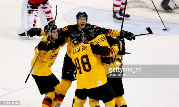 Jonas Muller of Germany celebrates his goal with teammates Brooks Macek Frank Mauer during the Men's Ice Hockey Gold Medal match between Germany and...