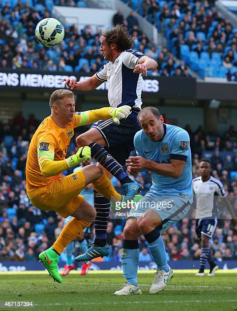 Jonas Olsson of West Brom collides with Joe Hart and Pablo Zabaleta of Manchester City during the Barclays Premier League match between Manchester...