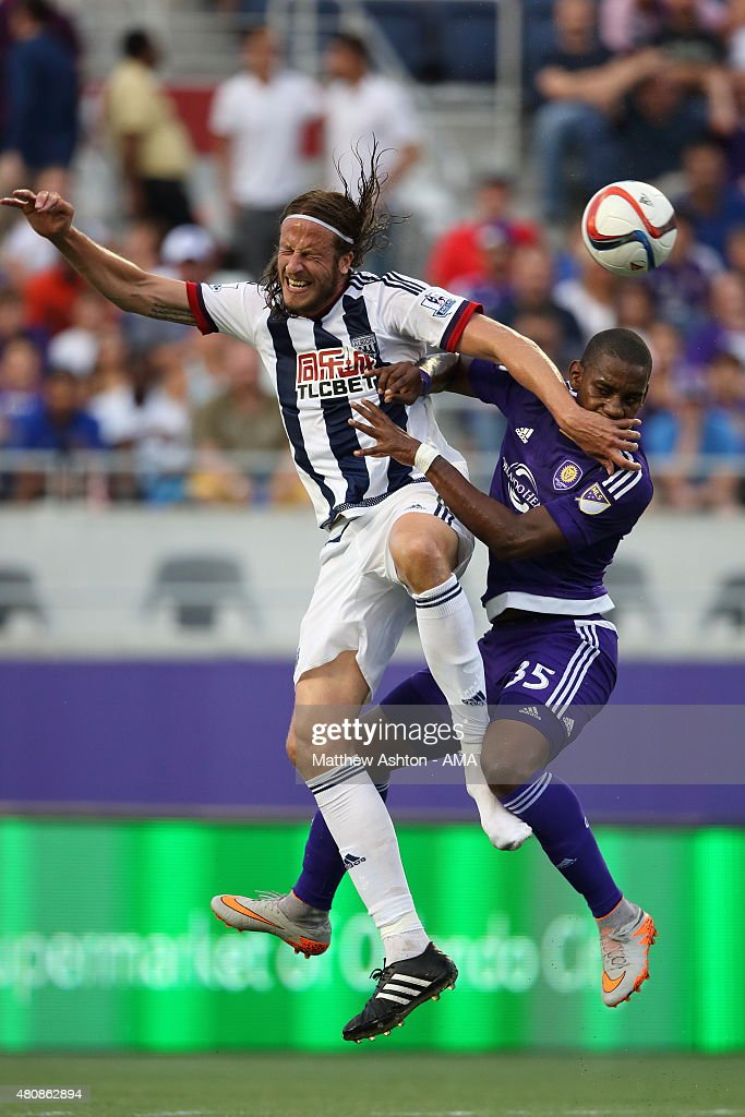 Jonas Olsson of West Bromwich Albion and Bryan Rochez of Orlando City as Olsson loses his boot during the pre-season friendly between Orlando City and West Bromwich Albion at Orlando Citrus Bowl on July 15, 2015 in Orlando, Florida.