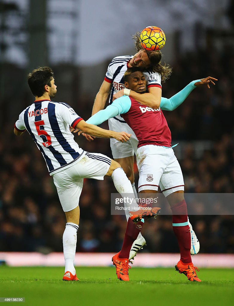 Jonas Olsson of West Bromwich Albion climbs over Diafra Sakho of West Ham United as Claudio Yacob of West Bromwich Albion looks on during the Barclays Premier League match between West Ham United and West Bromwich Albion at Boleyn Ground on November 29, 2015 in London, England.