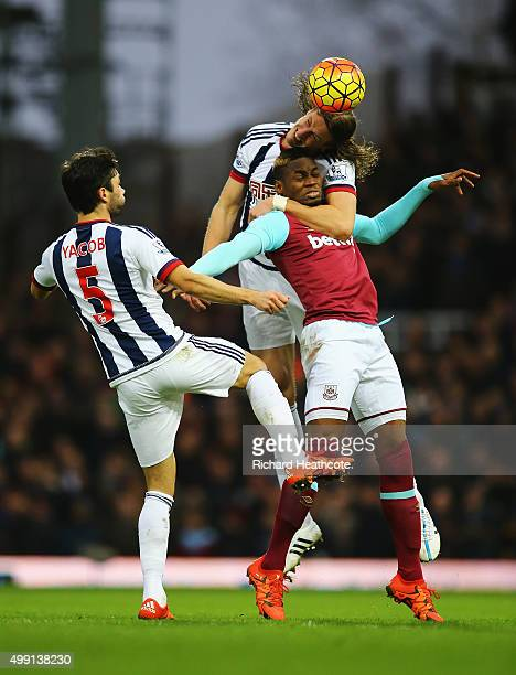 Jonas Olsson of West Bromwich Albion climbs over Diafra Sakho of West Ham United as Claudio Yacob of West Bromwich Albion looks on during the...
