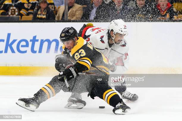 Jonas Siegenthaler of the Washington Capitals commits a holding foul against Brad Marchand of the Boston Bruins during the first period at TD Garden...