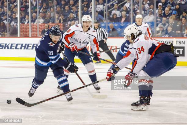 Jonas Siegenthaler of the Washington Capitals pokes the puck away from Bryan Little of the Winnipeg Jets during first period action at the Bell MTS...