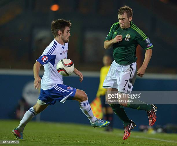 Jonas Tor Naes tackles Niall McGinn during the Euro 2016 Qualifier between Northern Ireland and Faroe Islands at Windsor Park on October 11 2014 in...
