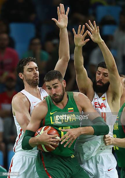 Jonas Valanciunas of Lithuania handles the ball under pressure from Pau Gasol and Nikola Mirotic of Spain during the Men's Preliminary Round Group B...