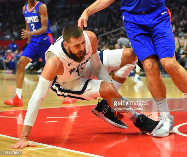 Jonas Valanciunas of the Memphis Grizzlies goes down with an injury as he steps on the foot of Ivica Zubac of the Los Angeles Clippers under the...