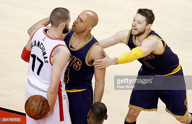 Jonas Valanciunas of the Toronto Raptors and Richard Jefferson of the Cleveland Cavaliers exchange words as Matthew Dellavedova holds back Jefferson...