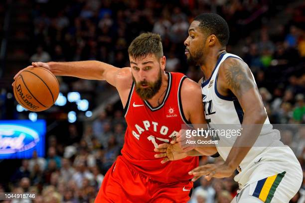 Jonas Valanciunas of the Toronto Raptors attempts to drie past Derrick Favors of the Utah Jazz during a game at Vivint Smart Home Arena on October 2,...