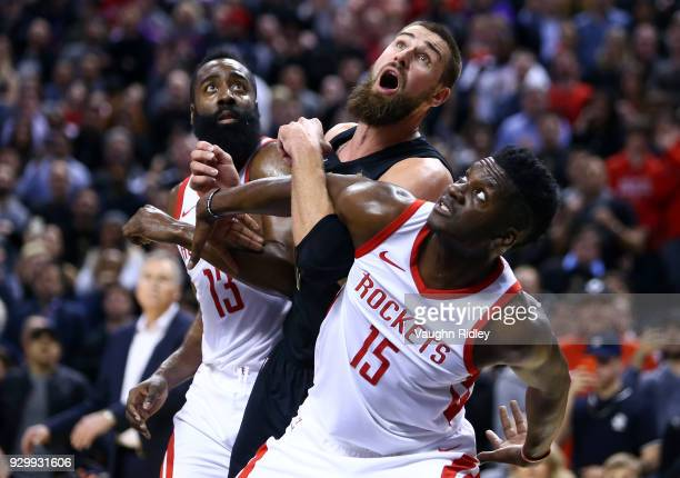 Jonas Valanciunas of the Toronto Raptors battles for a rebound with James Harden and Clint Capela of the Houston Rockets during the second half of an...