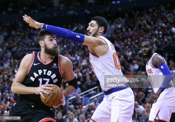 Jonas Valanciunas of the Toronto Raptors dribbles the ball as Enes Kanter of the New York Knicks defends during the second half of an NBA game at...