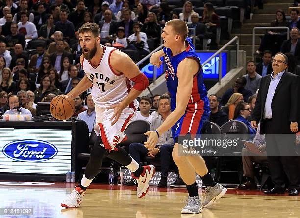 Jonas Valanciunas of the Toronto Raptors dribbles the ball as Henry Ellenson of the Detroit Pistons defends during the second half of an NBA game at...