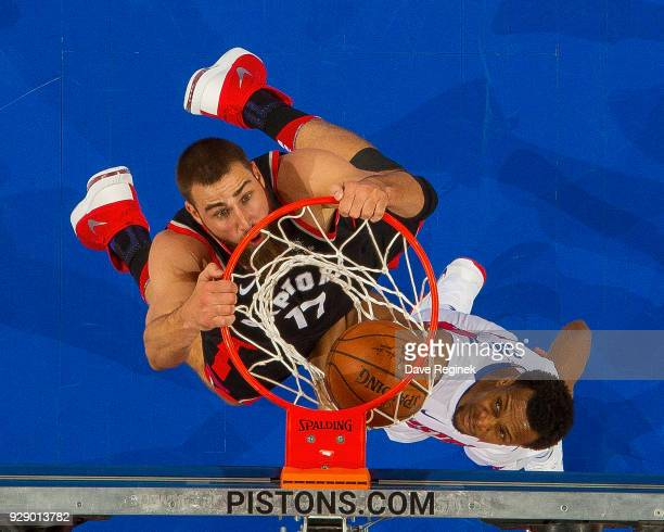 Jonas Valanciunas of the Toronto Raptors dunks the ball over Ish Smith of the Detroit Pistons in the first half of an NBA game at Little Caesars...