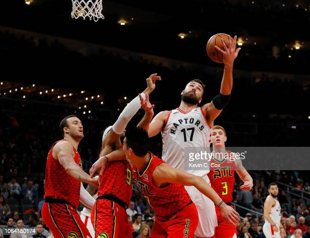 Jonas Valanciunas of the Toronto Raptors grabs a rebound against Jeremy Lin DeAndre' Bembry and Miles Plumlee at State Farm Arena on November 21 2018...