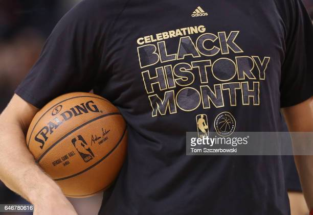 Jonas Valanciunas of the Toronto Raptors holds a ball as he warms up while wearing a Black History Month shirt before the start of their game against...