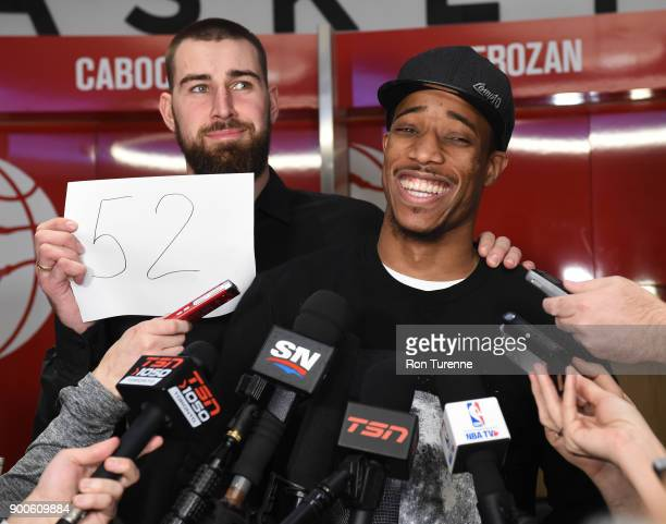 Jonas Valanciunas of the Toronto Raptors holds a sign during the post game press conference with DeMar DeRozan of the Toronto Raptors after DeRozan...