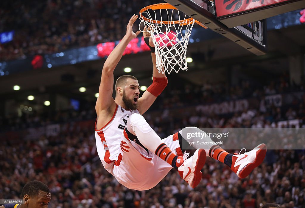 Jonas Valanciunas #17 of the Toronto Raptors holds on to the rim after dunking the ball against the Indiana Pacers in Game One of the Eastern Conference Quarterfinals during the 2016 NBA Playoffs on April 16, 2016 at the Air Canada Centre in Toronto, Ontario, Canada.